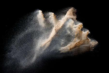 Sand flying explosion isolated on black background. Freeze motion of sandy dust splash.