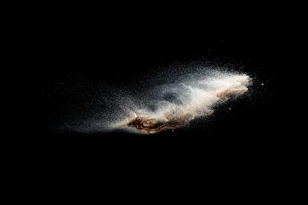 Sand explosion isolated on black background. Freeze motion of sandy dust splash. 免版税图像