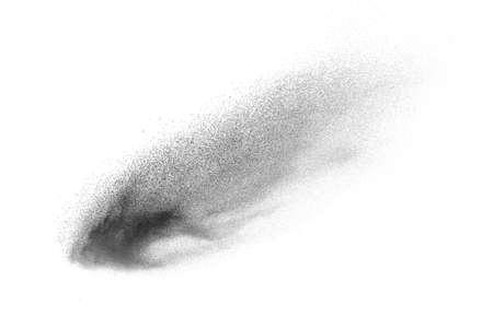 Black particles splatter on white background. Black powder dust exploding. 免版税图像