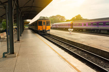 Thai local train on railway at sunset. 免版税图像