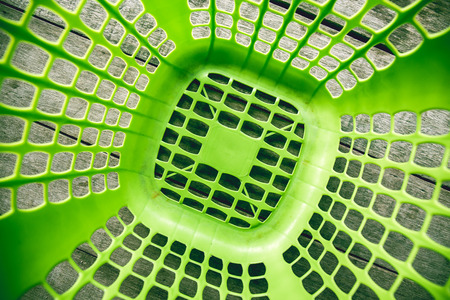 green clothes: Top view basket of green clothes on wood background
