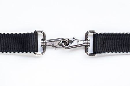 to clasp: Black belt rope strap lanyard, hanging metal clasp snap latch hook carabiner, isolated macro closeup latch Stock Photo