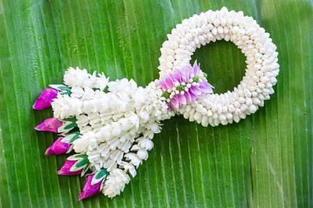soft light tone with Jasmine garland of flowers on banana leaf background