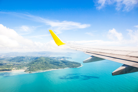high view: Wing of an airplane flying above the ocean Stock Photo
