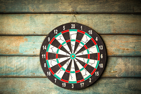The darts isolated on wooden background photo