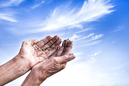 soiled: Soiled hands of elderly women with soft blue sky hope full in new better life