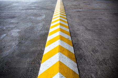 Een gele streep verkeersdrempel op betonweg.