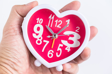 timekeeping: in time heart clock on hand background Stock Photo