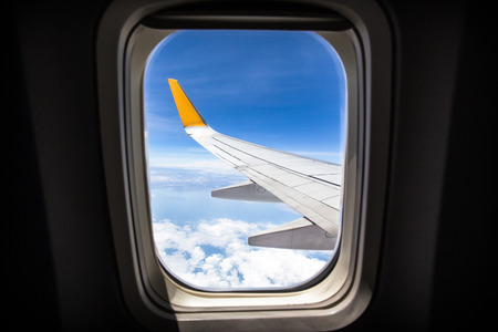 airplane engine: viewpoint Wing of windows airplane flying above the clouds in the sky