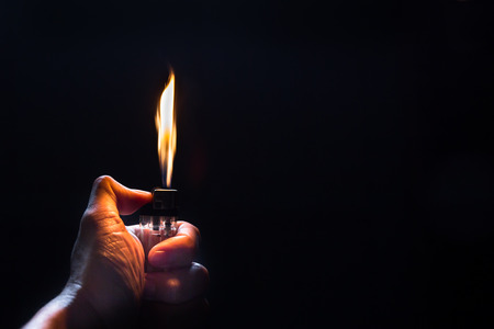 igniting: Hand with lighter igniting sparks on dark background Stock Photo