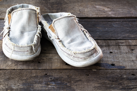squalor: vintage Dirty gym old shoes on wooden background