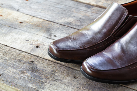 setup man: brown leather shoes on the wooden background