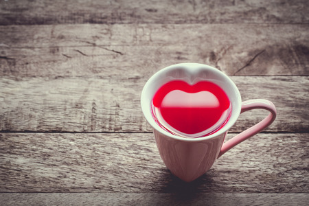 glass heart: vintage soft color tone with glass heart red nectar on wooden background