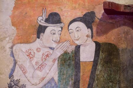 NAN, THAILAND - April 15, 2015: Mural painting of a man whispering to the ear of a woman at Wat Phumin in Nan Province, Northern Thailand.