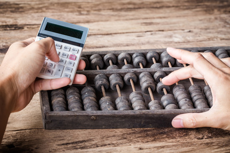 Mans hands accounting with old abacus and hold electronic calculator. picture financial concept
