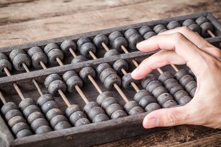 오래 된 abacus 회계와 남자의 손의 빈티지 톤 및 전자 계산기 개최. 사진 금융 개념 디자인. 스톡 콘텐츠