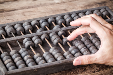Vintage tone of Man's hands accounting with old abacus and hold electronic calculator. picture financial concept design. Standard-Bild