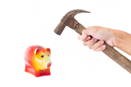 Man hand holding a hammer will knock into Pig piggy bank saving. The concept of financial assets, reliability deposits, insurance savings.