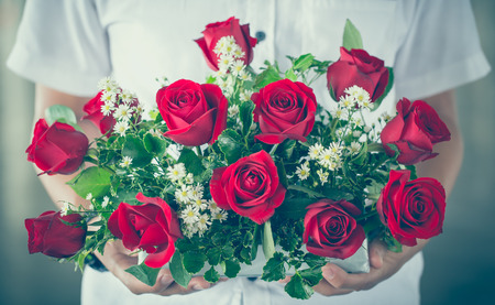 vintage tone of male hand giving bouquet of red roses Stock Photo