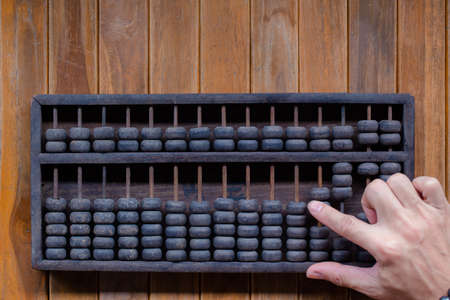 Old Vintage tone of Man's hands accounting with old abacus and hold electronic calculator. picture financial concept design. Reklamní fotografie