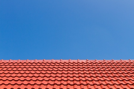 Red roof against blue sky photo