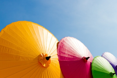 Colorful paper umbrella with blue sky background