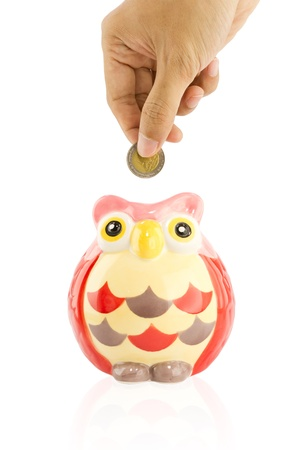 Hand insert coin into an owl piggy bank photo