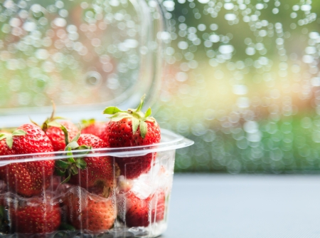 Strawberry in plastic package with raindrop bokeh in the background