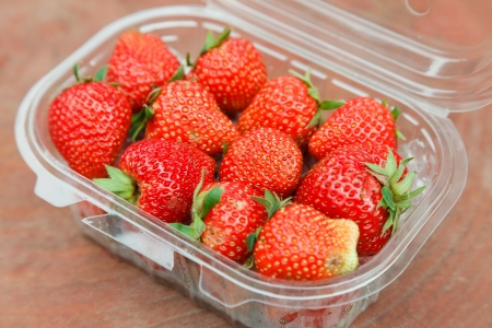 Strawberry in plastic package on the wood table