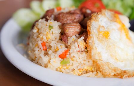 Close up of fried rice with pork and fired egg on top photo