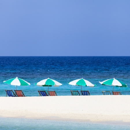 Colorful beach chairs and umbrellas on the beach photo