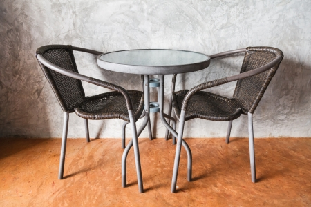 A table and chairs on the brown concrete floor with vintage wall background Stock Photo - 24810006