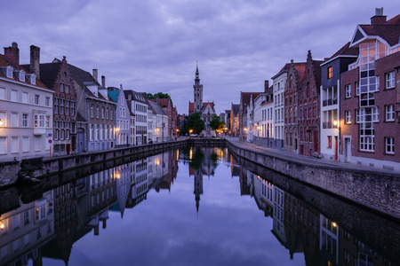 water town: Jan van Eyckplein, old town of Bruges, Belgium during sunset with reflection on water. Stock Photo