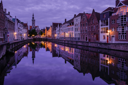 water town: Jan van Eyckplein, old town of Bruges, Belgium during sunset with reflection on water. Editorial