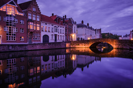 Jan van Eyckplein, old town of Bruges, Belgium during sunset with reflection on water. Stock Photo