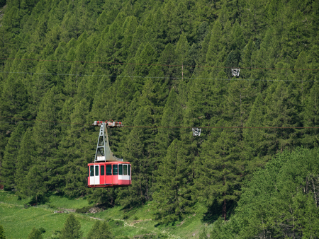 Cable car in Swiss Alps with pine forest in background, Zermatt, Switzerland.