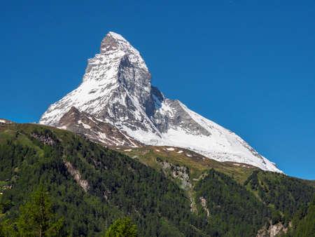Matterhorn peak in sunny day with pine tree mountain in foreground,  Zermatt, Switzerland.