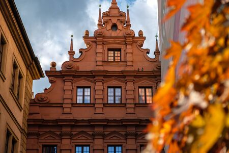 Old city hall rathaus of Wurzburg, Germany with red autumn leaves in the foreground.
