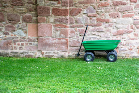 A green garden pushcart, wheelbarrow on the green grass field with old brick wall in the background. Stock Photo
