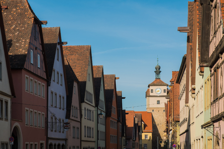 Colorful building and clock tower in old street of Rothenburg ob der Tauber, Bavaria, Germany with bright clear blue sky.