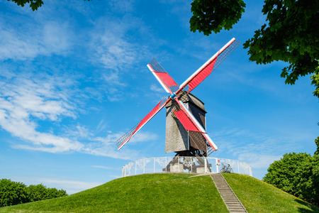 Sint-Janshuis Mill, windmill with few cloud and blue sky background in Brugge, Belgium.