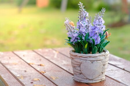 Artificial lavender flowers in metal vase on wood table with sunshine backlit. Stock Photo - 133880233
