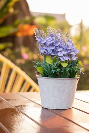 Artificial lavender flowers in metal vase on wood table with sunshine backlit.