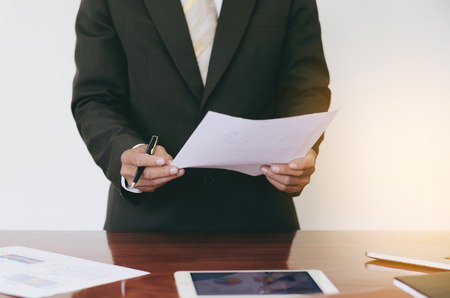 concep: Men standing at desk and  reading document hand close up