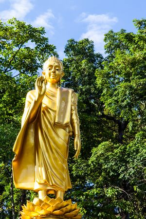 Standing Buddha in front of the forest photo