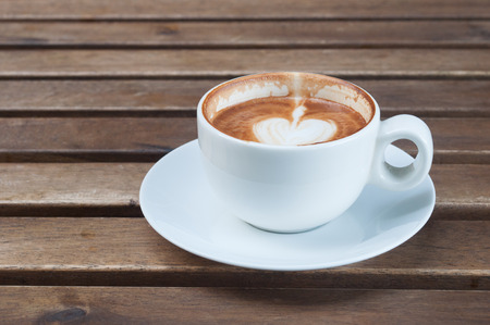 Wooden table with a cup of coffee photo