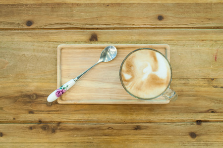 Glass of coffee on the wood table top view photo