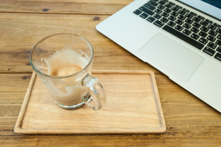energizing: Glass of coffee on the wood table on working time