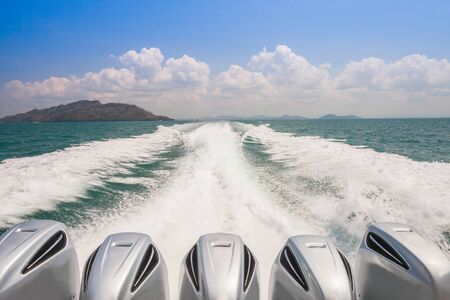 Engines of speed boat are driving along waving of water on ocean with mountain and cloudy sky located south of Thailand Stock Photo
