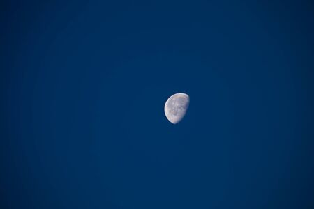A moon at day time on clear blue sky
